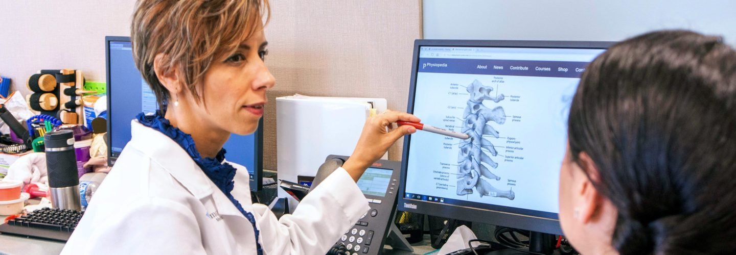 Doctor showing spinal diagram to patient