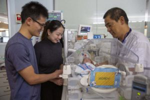 Parents and doctor visit infant in the NICU